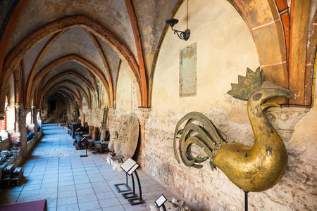 dom: Riga, Latvia - 25-August-2015: old bronze Chicken weathercock and other ancient artifacts inside the inner courtyard Gallery of Riga Cathedral. Riga, Latvia. Editorial