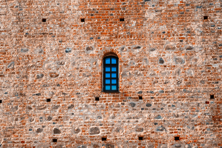 red brick: Arched window in a aged red brick castle wall