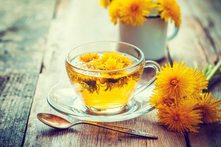 Cup of healthy dandelion tea. Herbal medicine. Retro toned. Stock Photo - 58723396