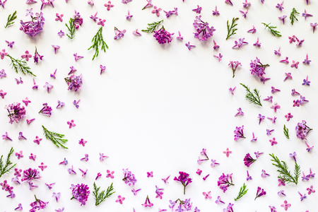 Floral border of fresh lilac flowers and green twigs on white. Flat lay, top view.