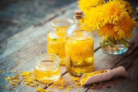 Flessen paardenbloem tinctuur of olie, bloem bos, houten lepel en honing op tafel. Kruidenmedicijn. Stockfoto