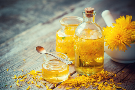 Dandelion tincture or oil bottles, mortar and honey on table. Herbal medicine.