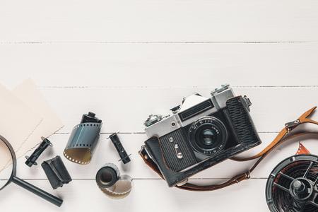 Retro camera, oude foto film rollen, lege foto's en vergrootglas op houten achtergrond. Plat leggen, bovenaanzicht.