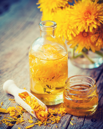 Bottle of dandelion tincture or oil, flower bunch and honey jar on table. Herbal medicine. Retro styled photo.