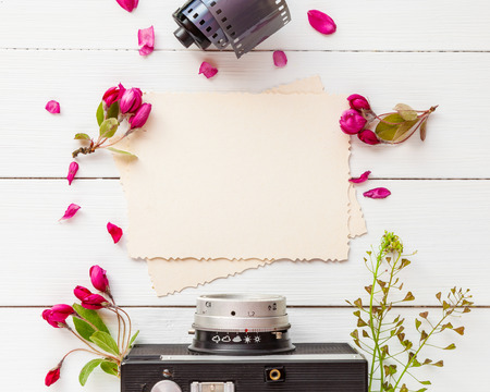 Old empty photo frame for the inside, retro camera, photo film rolls and apple flowers on white background. Flat lay, top view.