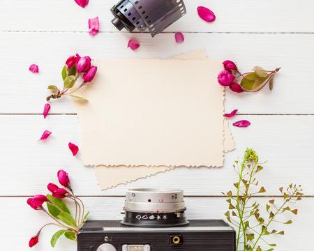 Old cadre photo vide pour l'intérieur, rétro appareil photo, photo rouleaux de film et de fleurs de pomme sur fond blanc. à plat, vue de dessus.