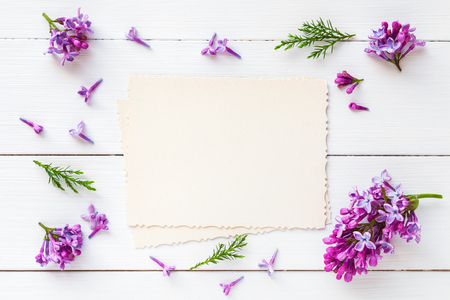 Old empty photo for the inside and frame of fresh lilac flowers on white wooden background. Flat lay, top view.