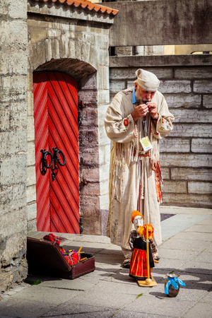 puppet master: Tallinn, Estonia - June 2, 2016: Puppet master and string marionette doll in the Historical Center of Tallinn city. Tallinn, Estonia.