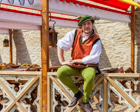 barker: Tallinn, Estonia - June 2, 2016: cheerful man in national medieval clothing near medieval restaurant in the Historical Center of Tallinn city. Tallinn, Estonia.