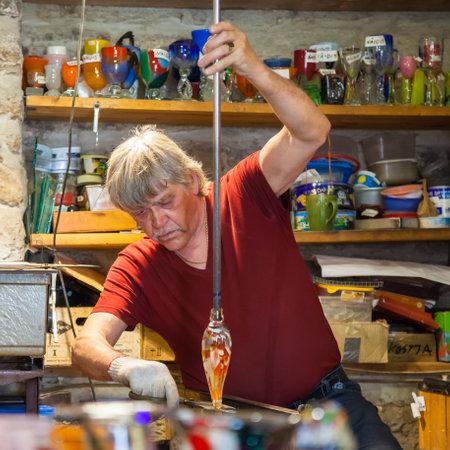 glassblower: Tallinn, Estonia - June 2, 2016: Glassblower forming molten glass in his workshop in the Historical Center of Tallinn city. Tallinn, Estonia. Editorial