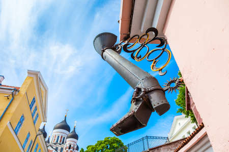 Rain water downspout as boot and view towards Alexander Nevsky Cathedral and medieval house. Tallinn, Estonia.