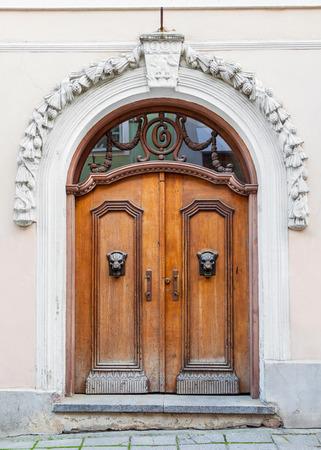 heads old building facade: Vintage wooden door and old building facade in old Tallinn city, Estonia Stock Photo