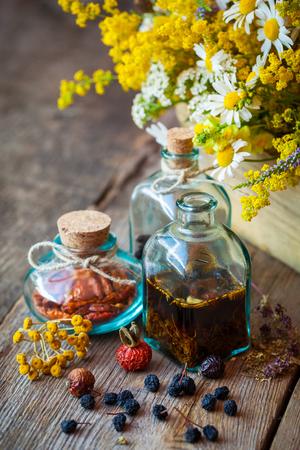 elixir: Botellas de tintura y hierbas secas, manojo de hierbas curativas en caja de madera sobre la mesa. Medicina herbaria. enfoque selectivo. Foto de archivo