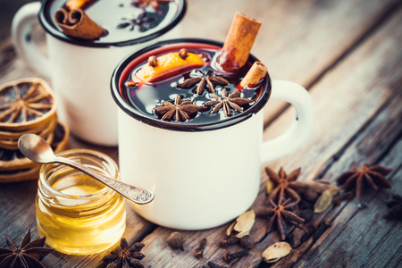 Mulled wine in mugs, dry spice and honey jar. Stock Photo