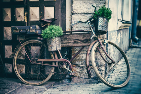 old suitcase: Vintage stylized photo of old bicycle carrying flower pots and suitcase as decoration and wooden plank for writing the text inside Stock Photo