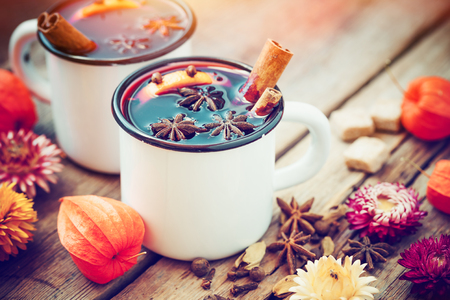 skillet: Mulled wine in mugs, spice and dry flowers. Autumn still life.