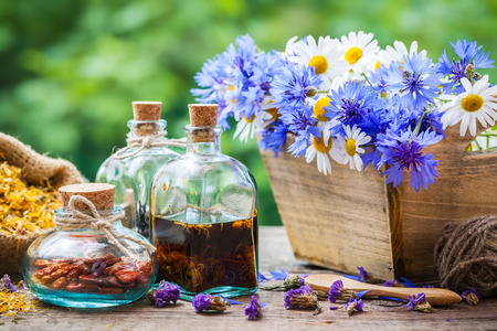 Bottles of tincture and dry healthy herbs, bunch of healing flowers in wooden box on table. Herbal medicine.