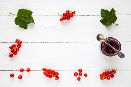 redcurrant: Red currant jam and fresh redcurrant berries as border with copy space on white table. Flat lay, top view.