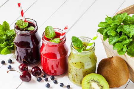 Healthy smoothie from summer fruits and berries in a jars with straws Stock Photo
