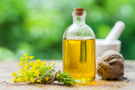 Bottle of rapeseed oil (canola) and repe flowers on table outdoors Stock Photo - 61088854