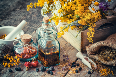 Bottles of tincture and dry healthy herbs, wooden scoop, bunch of healing herbs in wooden box on table. Herbal medicine. Retro styled. Selective focus. Imagens