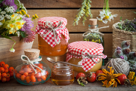 Jars of honey, bottles of healthy herbs and healing herbs bunches. Herbal medicine and nutraceuticals. Stock Photo