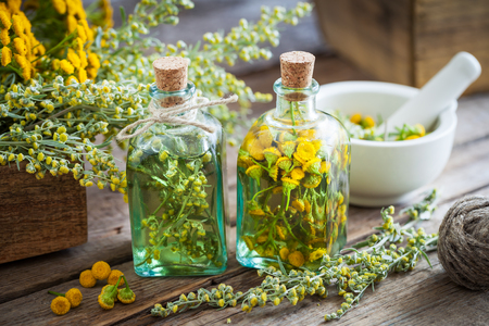 pocima: botellas del tinte de tanaceto y estragón hierbas saludables, la curación de ajenjo hierbas en caja de madera y en el mortero. Medicina herbaria.