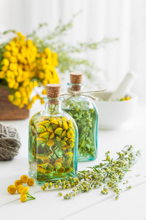 Tincture bottles of tansy and tarragon healthy herbs, healing herbs in wooden box and in mortar. Herbal medicine.