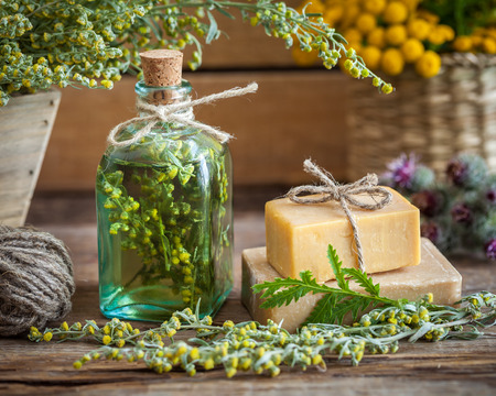 Bottle of tarragon tincture, healthy herbs and bars of homemade soap. Herbal medicine and natural care products.