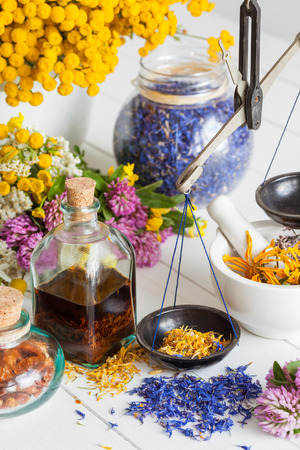 Bottles of tincture, mortar, jar of healthy herbs and scales on table. Herbal medicine. Selective focus.
