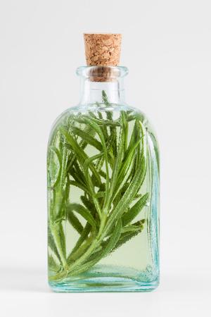elixir: Botella de aceite de romero o infusión primer plano esencial en blanco.