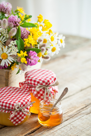 Jars of honey and summer healing herbs bunch on table. Selective focus. Stock Photo