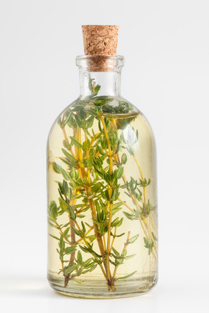 Bottle of thyme essential oil or infusion closeup on white.