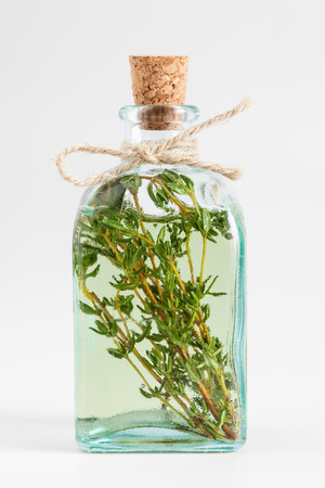 Transparent bottle of thyme essential oil or infusion on white. Foto de archivo