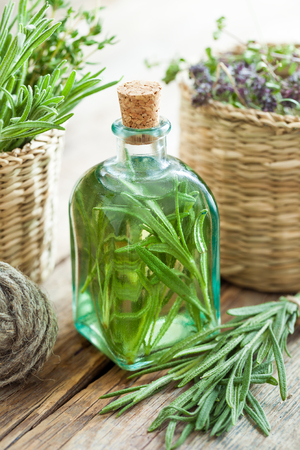 Bottle of essential rosemary oil or infusion and basket with healing herbs closeup.
