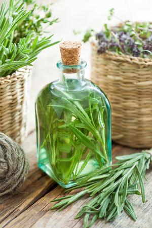 Fles essentiële rozemarijn olie of infusie en mandje met helende kruiden close-up. Stockfoto