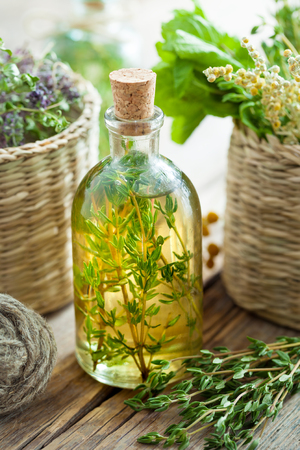 Bottle of thyme essential oil or infusion and basket with healing herbs.