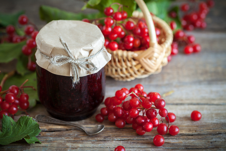 guelder: Jar of Guelder rose (Red Viburnum) jam and basket with red healthy berries on background. Stock Photo