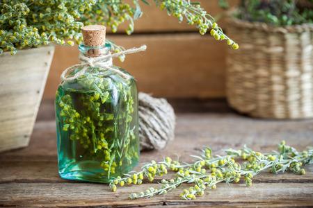 ajenjo: Botella de ausente o tintura de estragón, ajenjo hierbas curativas en tabla de madera. Medicina herbaria.