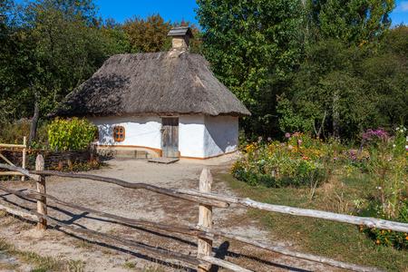 Retro ukrainian cottage with thatched roof and garden in Pirogovo village, Kiev region, Ukraine.