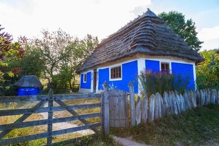 Traditional ukrainian cottage with thatched roof in Pirogovo village, Kiev region, Ukraine.