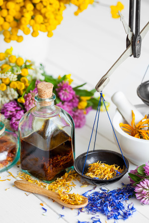 Bottle of tincture or potion, mortar, healthy herbs and scales on table. Herbal medicine. Selective focus. Stock Photo