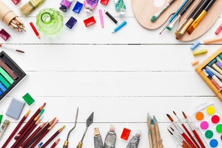 Waterverf en olieverf, penselen voor het schilderen, potloden, pastelkrijt op witte tafel. Bovenaanzicht. Vlak liggen.