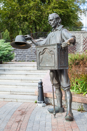 golden key: KIEV, UKRAINE - SEPTEMBER 23, 2016: sculpture of organ grinder Father Carlo, fairy tale character of Alexei Tolstoy store The Golden Key near entrance to Kiev puppet theater in Kiev, Ukraine.