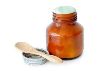 salve: A balm jar full of medicated ointment in green color and spoon on white background. Stock Photo