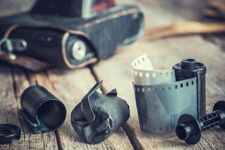 darkroom: Old photo film rolls and cassette, vintage camera on background. Retro toned.