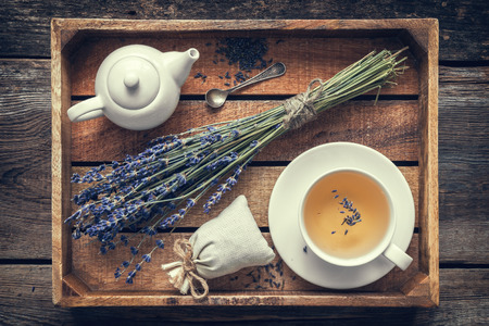 sachets: Bunch of lavender flowers, healthy tea in cup, teapot and sachets filled with dried lavender in wooden tray. Retro toned. Top view. Flat lay. Stock Photo