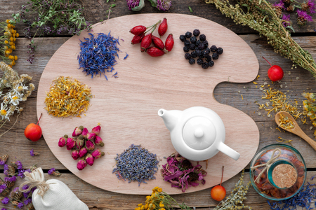 Healing herbs on wooden palette and tea kettle, top view. Herbal medicine concept. Stock Photo