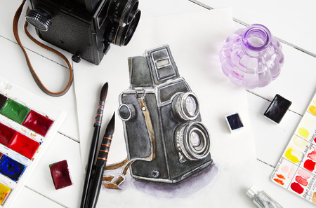 photography themes: Watercolor sketch of retro camera, old photo camera, paintbrushes and watercolor paints. Flat lay, top view.