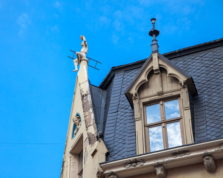 roof windows: Old garret roof with sculptures and windows, Riga, Latvia.